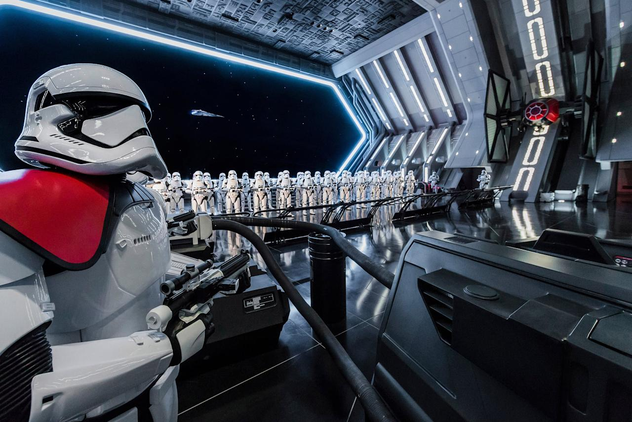 """<p>While on our tour of <a href=""""https://www.popsugar.com/family/Disney-Star-Wars-Galaxy-Edge-Attractions-45503328"""" class=""""ga-track"""" data-ga-category=""""Related"""" data-ga-label=""""http://www.popsugar.com/family/Disney-Star-Wars-Galaxy-Edge-Attractions-45503328"""" data-ga-action=""""In-Line Links"""">Star Wars: Rise of the Resistance</a>, we were told there was something for us just beyond the doors of our transport. After getting very close to the doors of the transport they whooshed open in typical Star Wars fashion to reveal the hangar bay in the Star Destroyer! </p> <p>The back of the hangar bay is a screen that looks out into space, there's legions of Storm Troopers armed with their blasters, massive TIE Fighters up on the wall, glassy black flooring, and First Order officers telling you what to do next. This reveal is one that many Star Wars fans will remember for years to come!</p> <p>This is where you'll enter your trackless ride vehicle that is operated by a droid who might not be as smart as the other droids in the Star Wars galaxy. Kids will love meeting this new R5 droid and scurrying around the First Order with them.</p>"""