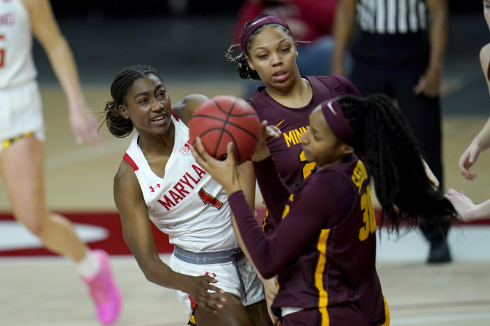 Maryland guard Diamond Miller, left, competes for a rebound with Minnesota center Klarke Sconiers, center, and forward Kadiatou Sissoko during the second half of an NCAA college basketball game, Saturday, Feb. 20, 2021, in College Park, Md. (AP Photo/Julio Cortez)
