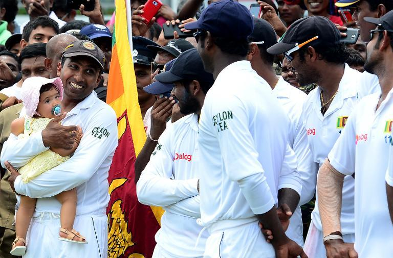Sri Lanka's cricketer Mahela Jayawardene (L) holds his daughter Sansana as his teammates and wife look on at the Sinhalese Sports Club (SSC) Ground in Colombo on August 18, 2014