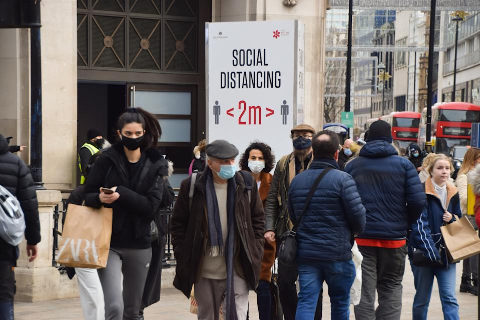 LONDON, UNITED KINGDOM - 2020/12/02: People walk past a Social Distancing sign on Oxford Street. Thousands of people poured into West End stores as England eased its month-long lockdown. (Photo by Vuk Valcic/SOPA Images/LightRocket via Getty Images)