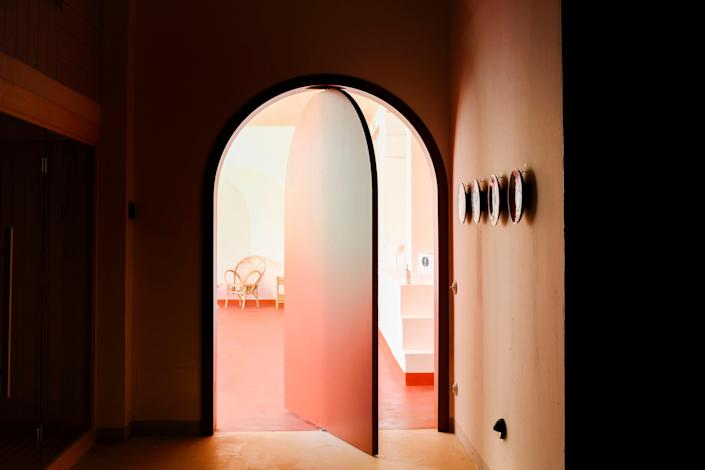 """<div class=""""caption""""> """"The typical Menorca architecture, with round doors, the marès (a sandstone from the Balearic Islands), and the colors that can be seen in the town of Ciutadella de Menorca (such as dark red and dark green), characterized the spaces,"""" Dorothée says. </div> <cite class=""""credit"""">KAREL-BALAS</cite>"""