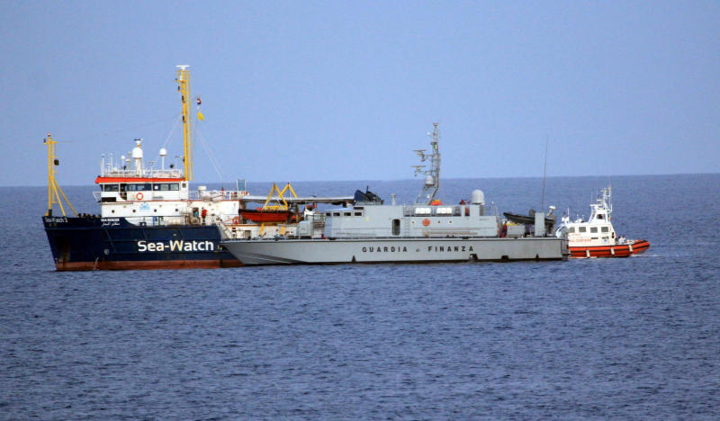 In this Sunday, May 19, 2019 photo, a Guardia di Finanza patrol boat approaches the German aid group ship Sea-Watch 3 in the waters off the Sicilian island of Lampedusa, southern Italy. Italy's hard-line Interior Minister Matteo Salvini threatened possible legal action Monday, May 20, 2019 after 47 migrants rescued at sea by the humanitarian aid ship landed on the southern Italian island of Lampedusa on Sunday evening with the cooperation of the Coast Guard and financial police despite his explicit ban against them. (Elio Desiderio/ANSA via AP)