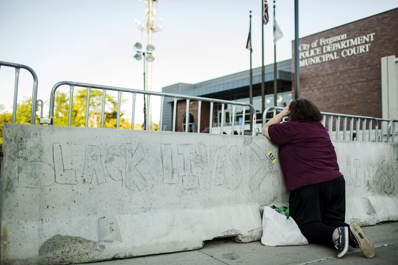 A woman kneels to pray in front of the Ferguson Police Department before another night of demonstrations in Ferguson, Missouri, August 11, 2015. St. Louis County Police released a video on Tuesday that they said shows a suspect, who has been accused of firing on police, drawing a pistol from his pants during protests in strife-torn Ferguson, Missouri. REUTERS/Lucas Jackson