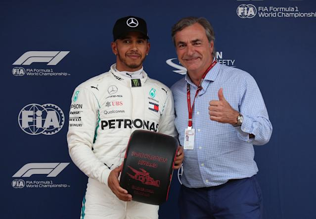 Formula One F1 - Spanish Grand Prix - Circuit de Barcelona-Catalunya, Barcelona, Spain - May 12, 2018 Mercedes' Lewis Hamilton poses with former Rally driver Carlos Sainz as he celebrates pole position after qualifying REUTERS/Albert Gea