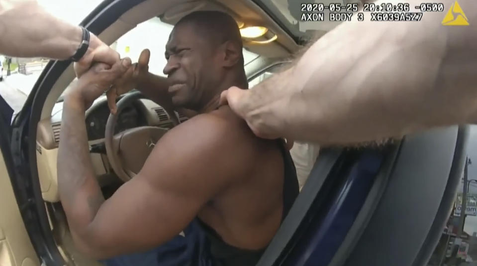 In this image from police body cam video, Minneapolis police officers attempt to remove George Floyd from a vehicle, on May 25, 2020, outside Cup Foods in Minneapolis, as it is shown Wednesday, March 31, 2021, during the trial of former Minneapolis police Officer Derek Chauvin in the case of Floyd's death, at the Hennepin County Courthouse in Minneapolis. (Court TV via AP, Pool)