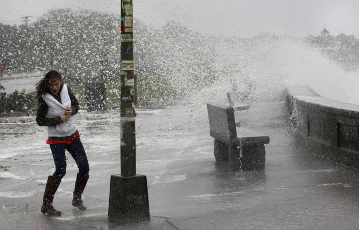 A woman reacts to waves crashing over a seawall in Narragansett, R.I., Monday, Oct. 29, 2012.  Hurricane Sandy continued on its path Monday, as the storm forced the shutdown of mass transit, schools and financial markets, sending coastal residents fleeing, and threatening a dangerous mix of high winds and soaking rain.  (AP Photo/Steven Senne)