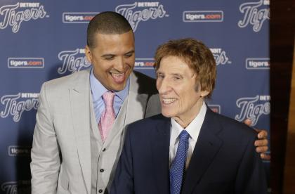 Victor Martinez (L) shares a laugh with Mike Ilitch after agreeing to terms on a new deal in 2014. (AP)