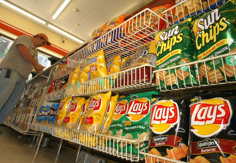 A convienence store customer make a purchase next to a shelf of Frito-Lay snacks, Tuesday, July 12, 2005, in Boston. PepsiCo Inc., which owns Frito-Lay snacks in addition to Quaker Foods and its flagship soft drink business, on Tuesday reported a 13 percent rise in second-quarter earnings. (AP Photo/Lisa Poole)