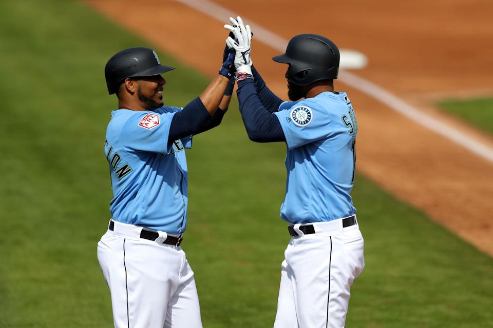 PEORIA, AZ - FEBRUARY 25: Domingo Santana #16 of the Seattle Mariners celebrates with Edwin Encarnacion #10 after hitting a home run during a Spring Training game against the Cincinnati Reds on Monday, February 25, 2019 at Peoria Sports Complex in Peoria, Arizona.  (Photo by Alex Trautwig/MLB Photos via Getty Images)