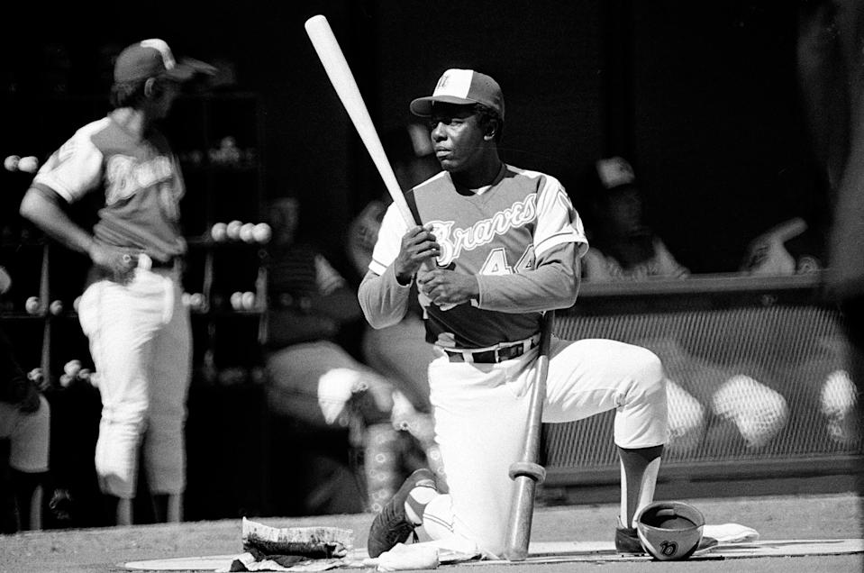 FILE - Atlanta Braves' right-handed slugger Hank Aaron (44) kneels in the batting circle as he waits for his turn at bat in a baseball game against the Cincinnati Reds at Riverfront Stadium in Cincinnati, Ohio, in this April 4, 1974, file photo. During the game Aaron tied the all-time home run record at 714. (AP Photo/File)