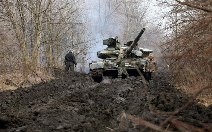 Ukrainian servicemen and a tank close to the front line with Russian-backed separatists near Lysychansk, Lugansk region  - AFP