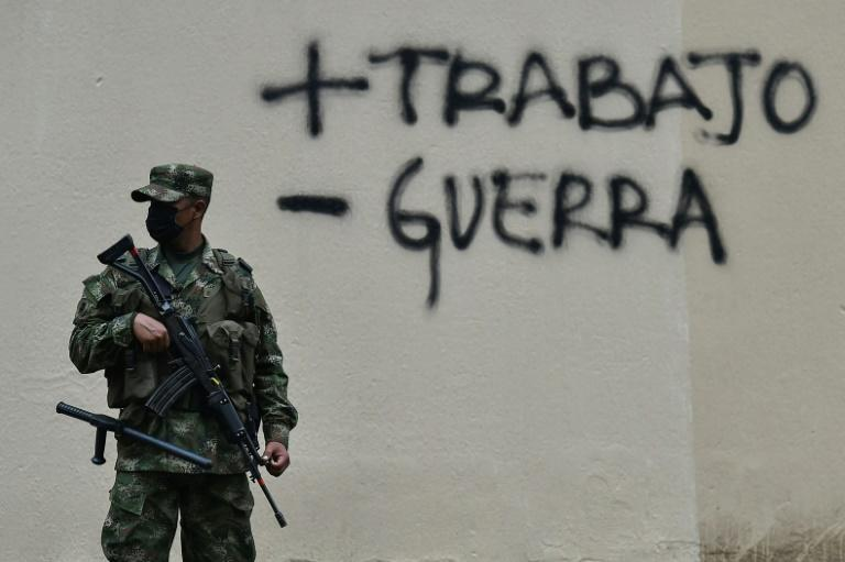 A soldier guards a street in Colombia after a protest against a tax reform bill