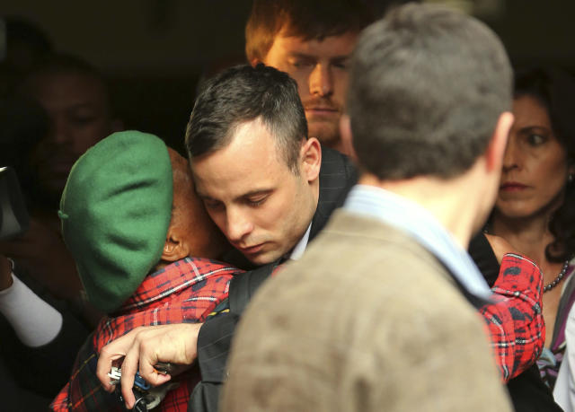 Oscar Pistorius, center, shares a hug with an unidentified woman as he leaves the high court in Pretoria, South Africa, Wednesday, April 16, 2014. Pistorius is charged with murder for the shooting death of his girlfriend, Reeva Steenkamp, on Valentines Day in 2013. (AP Photo/Themba Hadebe)