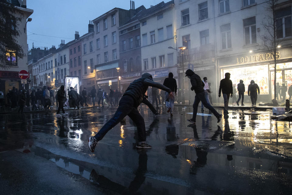 Protestors thrown stones in the Belgium capital, Brussels, Wednesday, Jan. 13, 2021, at the end of a protest asking for authorities to shed light on the circumstances surrounding the death of a 23-year-old Black man who was detained by police last week in Brussels. The demonstration in downtown Brussels was largely peaceful but was marred by incidents sparked by rioters who threw projectiles at police forces and set fires before it was dispersed. (AP Photo/Francisco Seco)