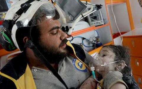 A member of the Syrian civil defence, known as the White Helmets, helps an injured Syrian child after pulling him out from under the rubble - Credit: OMAR HAJ KADOUR/AFP/Getty Images