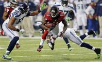 Atlanta Falcons wide receiver Julio Jones (11) works against Seattle Seahawks outside linebacker K.J. Wright (50) and free safety Earl Thomas (29) during the second half of an NFC divisional playoff NFL football game Sunday, Jan. 13, 2013, in Atlanta. (AP Photo/John Bazemore)