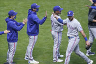 Texas Rangers' Joey Gallo, right, goes through the celebration line after making a diving catch of a ball off the bat of Minnesota Twins' Miguel Sano to end the baseball game in 10 innings Thursday, May 6, 2021, in Minneapolis. (AP Photo/Jim Mone)