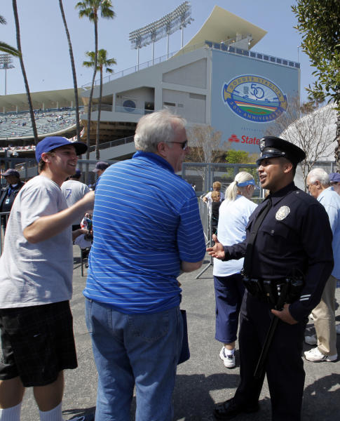 Los Angeles Police Officer Mel Campos chats with Dodger fans arriving for the home opener baseball game at Dodger Stadium Tuesday, April 10, 2012. Police were out in force, swarming on bikes, going undercover and cracking down on boozing tailgaters a year after a Giants fan was beaten into a coma in the parking lot. (AP Photo/Reed Saxon)