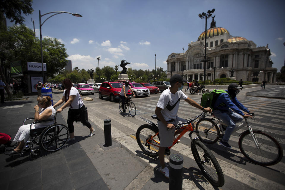 Mexicans are seen out and about after the easing of COVID-19 related restrictions, near the Bellas Artes Palace in downtown Mexico City, Friday, July 3, 2020. Limited reopening of restaurants and other businesses in the capital this week came as new coronavirus cases continued to climb steadily. (AP Photo/Fernando Llano)