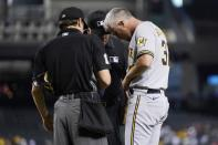 Milwaukee Brewers relief pitcher Trevor Richards, right, turns his belt around as umpires D.J. Reyburn, left, and Brian O'Nora, center, examine his belt, glove and cap during the second inning of a baseball game against the Arizona Diamondbacks, Monday, June 21, 2021, in Phoenix. Beginning Monday, Major League Baseball will enhance its enforcement of rules that prohibit applying foreign substances to baseballs. (AP Photo/Ross D. Franklin)