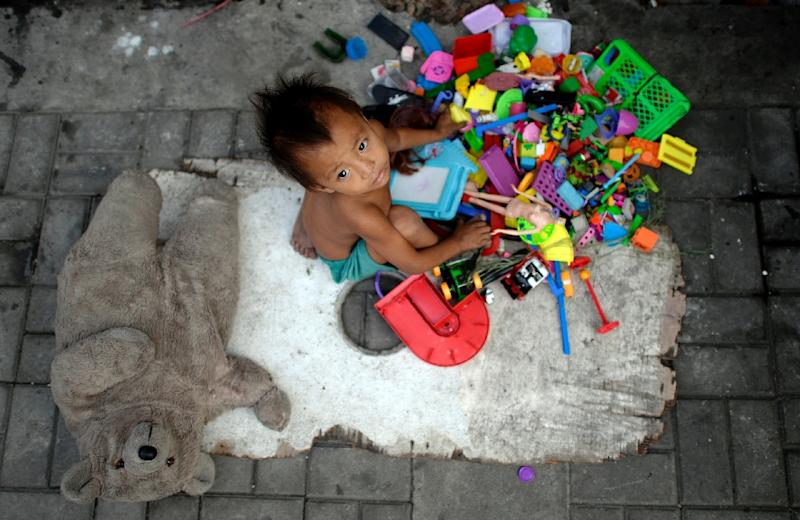A homeless boy plays with his toys in Manila (AFP Photo/Noel Celis)