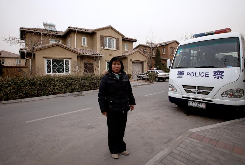 In this Saturday, March 9, 2013 photo, Zhao Meifu, a farmer from Gansu province, stands in front of a house in Beijing, where she claims to have been held with other petitioners before being sent to a labor camp last year in China's arid northwest. Zhao had been seeking redress for decades over a land grab by village officials. Tired of her complaints, police saw the labor camp as a quick way to get rid of her. Long hated and often abused, a notorious penal system that allows Chinese police to lock up people for up to four years without a trial or a judge's review has come under scrutiny. Cases like Zhao's last year have galvanized critics, many of them within the government, and China's newly installed leadership is seizing on the expectations for reform. (AP Photo/Andy Wong)
