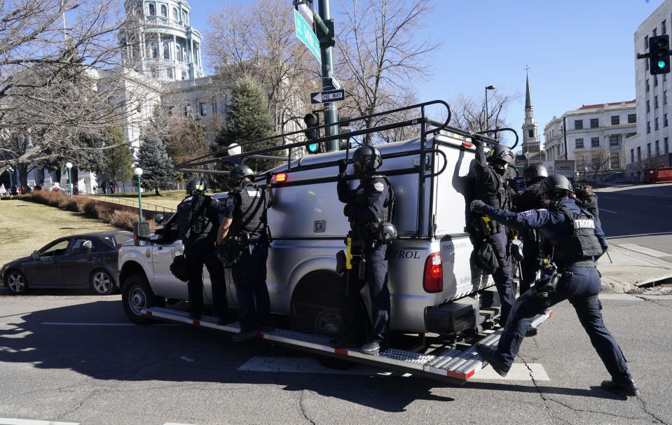 FILE - In this Jan. 6, 2021 file photo, Colorado State Patrol troopers hold on to a patrol vehicle as they keep watch on people attending a rally in support of President Donald Trump outside the State Capitol in downtown Denver. Statehouses where Trump loyalists have rallied since the Nov. 3 election are heightening security after the storming of the U.S. Capitol this week. Police agencies in a number of states are monitoring threats of violence as legislatures return to session and as the nation prepares for the inauguration of President-elect Joe Biden. (AP Photo/David Zalubowski, File)