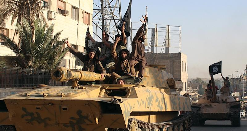 Islamic State militants patrol the Syrian city of Raqa