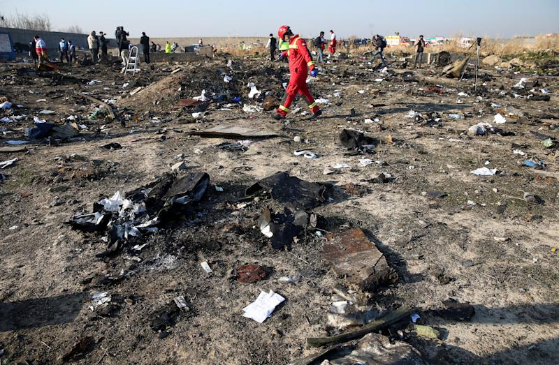 A member of a rescue team walks among debris from a plane belonging to Ukraine International Airlines, that crashed after a take-off from Iran's Imam Khomeini airport, on the outskirts of Tehran, Iran January 8, 2020. Nazanin Tabatabaee/WANA (West Asia News Agency) via REUTERS ATTENTION EDITORS - THIS IMAGE HAS BEEN SUPPLIED BY A THIRD PARTY