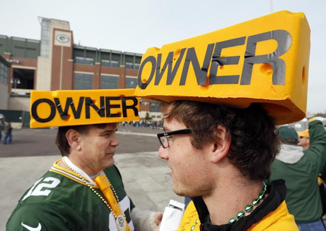 Andrew Floren, left, and son Samuel Floren tailgate before before an NFL football game between the Green Bay Packers and the Cleveland Browns Sunday, Oct. 20, 2013, in Green Bay, Wis. (AP Photo/Mike Roemer)