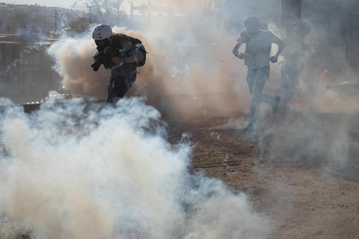 A photojournalist is surrounded in a cloud of tear gas released by U.S. Customs and Border Protection after some migrants, part of a caravan of thousands from Central America, attempted to illegally cross the border into the U.S. from Tijuana, Mexico, on Sunday. (Photo: Adrees Latif/Reuters)