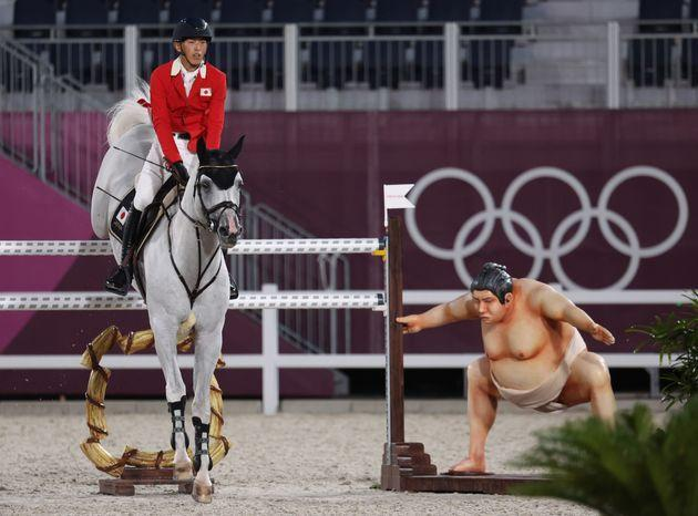 A rider clears the barrier as the statue of a sumo wrestler looks in the Tokyo Olympics equestrian competition. ) (Photo: picture alliance via Getty Images)