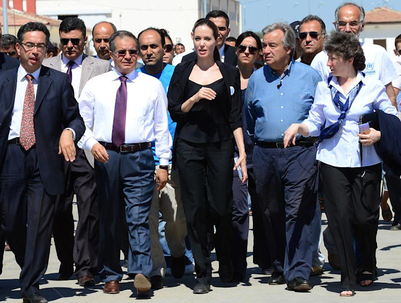 Hollywood star Angelina Jolie, center left, in her role as special envoy for the U. N. refugee agency, and UNHCR chief Antonio Guterres, center right, at the  Oncupinar Syrian refugee camp in Kilis, Turkey, Thursday,  Sept. 13, 2012. Jolie met with Syrian refugees in Turkey, after visiting Syrian refugee camps in Jordan and Lebanon. There are more than 80,000 Syrian refugees in 11 camps in Turkey. (AP Photo/Dilek Mermer, Pool)