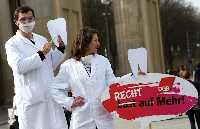 Two demonstrators posing as unequally paid dentists, the woman holding a sign reading 'Not a Wish But a Right to More!', demonstrate during the 'Equal Pay Day' demonstration on March 21, 2014 in Berlin.