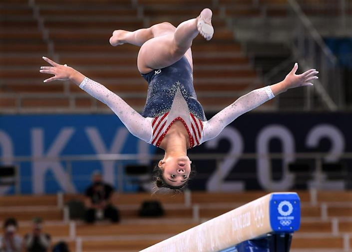 Sunisa Lee is shown upside down above the beam.