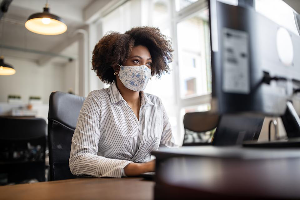 Businesswoman with face mask working at her desk looking at computer monitor, in office. Female professional back to work after covid-19 pandemic lockdown.