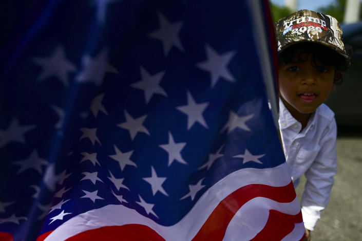 A boy carries the U.S. flag while wearing a pro-Trump cap moments before leaving for the headquarters of the Republican party in support of President Donald Trump's candidacy a few weeks before the presidential election next November, in Carolina, Puerto Rico, Sunday, Oct. 18, 2020. President Donald Trump and former Vice President Joe Biden are targeting Puerto Rico in a way never seen before to gather the attention of tens of thousands of potential voters in the battleground state of Florida. (AP Photo/Carlos Giusti)