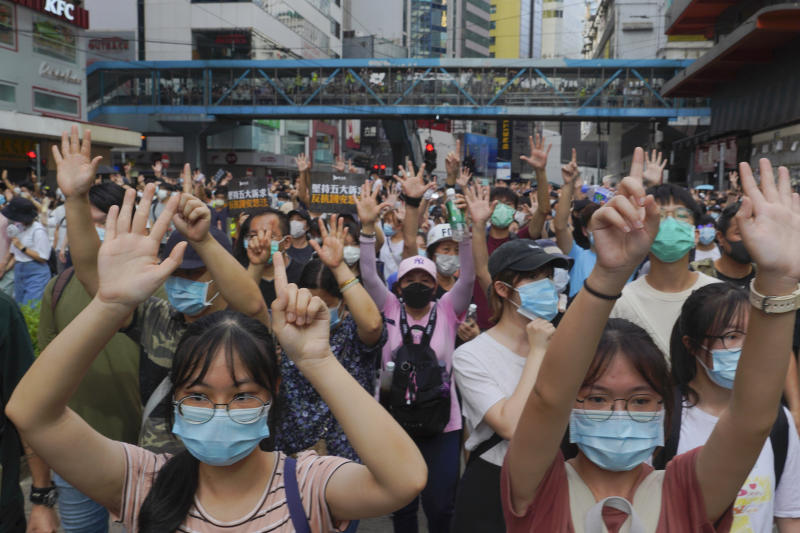 "Protesters against the new national security law march and gesture with five fingers, signifying the ""Five demands - not one less"" on the anniversary of Hong Kong's handover to China from Britain in Hong Kong, Wednesday, July. 1, 2020. Hong Kong marked the 23rd anniversary of its handover to China in 1997, and just one day after China enacted a national security law that cracks down on protests in the territory. (AP Photo/Vincent Yu)"