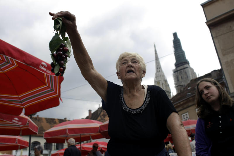 In this photo taken Thursday, June 6, 2013, a woman sells fresh cherries at a market in Zagreb, Croatia. A decade back when Croatia started negotiating the EU entry, then the war torn country was overjoyed at the prospect of becoming a member of European elite. With the EU in deep financial turmoil and Croatia's own economy in recession for five consecutive years, the excitement has dimmed as the Balkan country gets ready to officially become the 28th EU member on July 1. (AP Photo/ Marko Drobnjakovic)