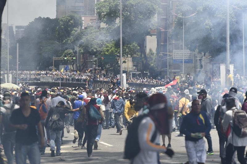 Demonstrators against Nicolas Maduro's government are seen amid a tear gas cloud during clashes with riot police in Caracas on April 8, 2017