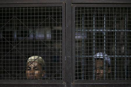 Rohingya Muslim illegal immigrants look out from the Immigration Detention Centre during the Muslim holy fasting month of Ramadan in Kanchanaburi province, in this file picture taken July 10, 2013. REUTERS/Athit Perawongmetha/Files