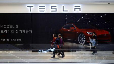 People walk past a planned store of Tesla in Hanam