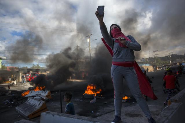<p>A supporter of presidential candidate Salvador Nasralla takes a selfie at a roadblock set up by people protesting what they call electoral fraud in Tegucigalpa, Honduras, Friday, Dec. 1, 2017. (Photo: Rodrigo Abd/AP) </p>