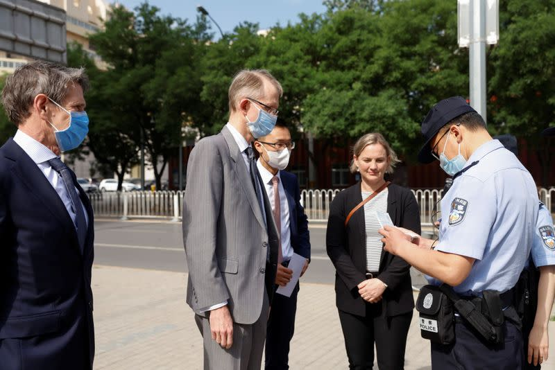 A police officer checks the ID of Australia's Ambassador to China, Graham Fletcher, outside the Beijing No. 2 Intermediate People's Court where Australian writer Yang Hengjun is expected to face trial on espionage charges, in Beijing