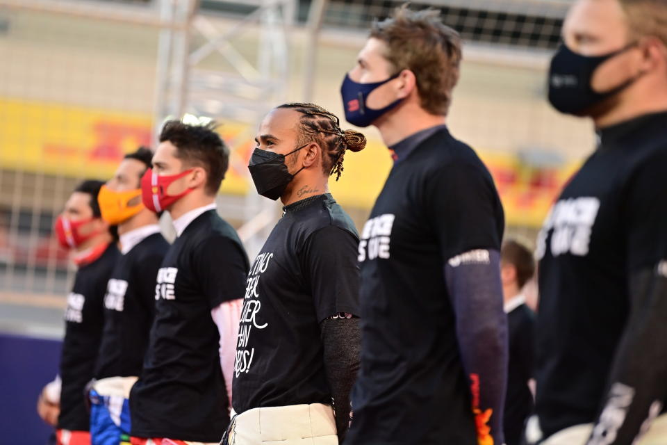 Mercedes driver Lewis Hamilton of Britain, center, and other drives attend at the starting grid prior to the start of the Bahrain Formula One Grand Prix at the Bahrain International Circuit in Sakhir, Bahrain, Sunday, March 28, 2021. (Andrej Isakovic, Pool via AP)