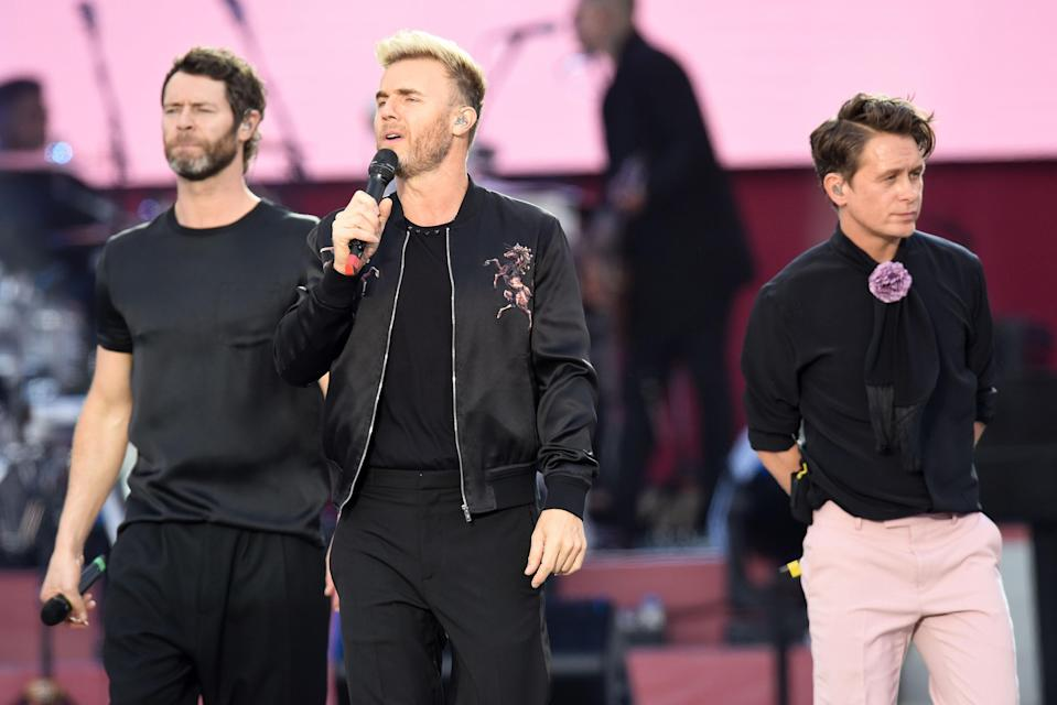 Take That performing on stage. (PA)