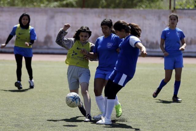 In this Thursday, May 2, 2019 photo, members of Hestia FC Women's Refugee Soccer and AO Vrilission players fight for the ball during a friendly game in Athens. Many of the players at Hestia FC weren't allowed to play or even watch soccer matches in their home countries. Hestia FC was set up by the Olympic Truce Centre, a non-government organization created in 2000 by the International Olympic Committee and Greek Foreign Ministry. (AP Photo/Thanassis Stavrakis)