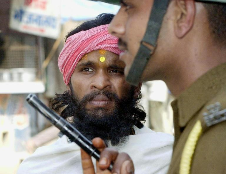 For decades Hindus and Muslims have been bitterly divided over the 16th-century Babri mosque - here a sadhu, a Hindu holy man, is stopped from entering the disputed site in March 2002