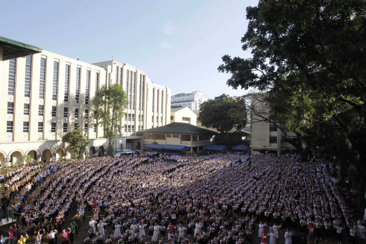 Thousands of students and faculty members dance to the theme song of the One Billion Rising campaign in the quadrangle of the St. Scholastica college in Manila February 14, 2013. One Billion Rising is a global campaign to call for an end to violence against women and girls, according to its organisers.  REUTERS/Romeo Ranoco (PHILIPPINES - Tags: POLITICS SOCIETY EDUCATION)