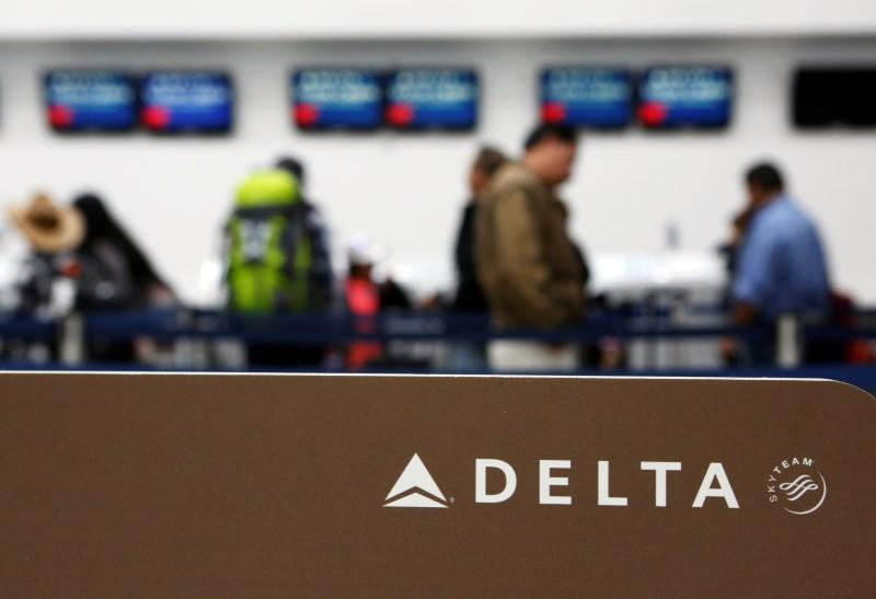 Passengers check in at a counter of Delta Air Lines in Mexico City